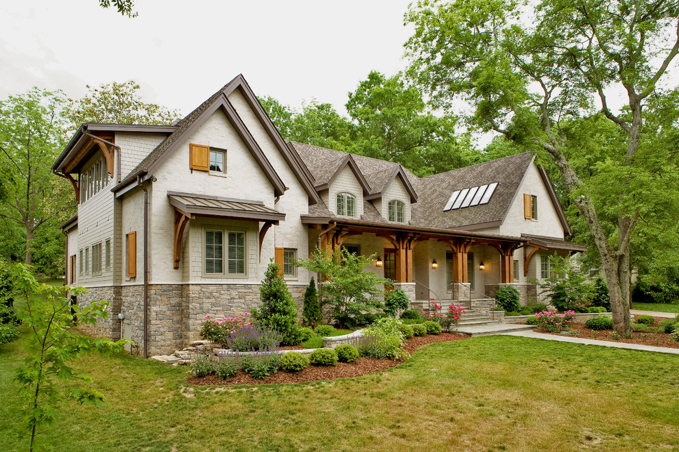 Mid-sized traditional beige two-story stone and clapboard exterior home idea in Nashville with a shingle roof and a brown roof
