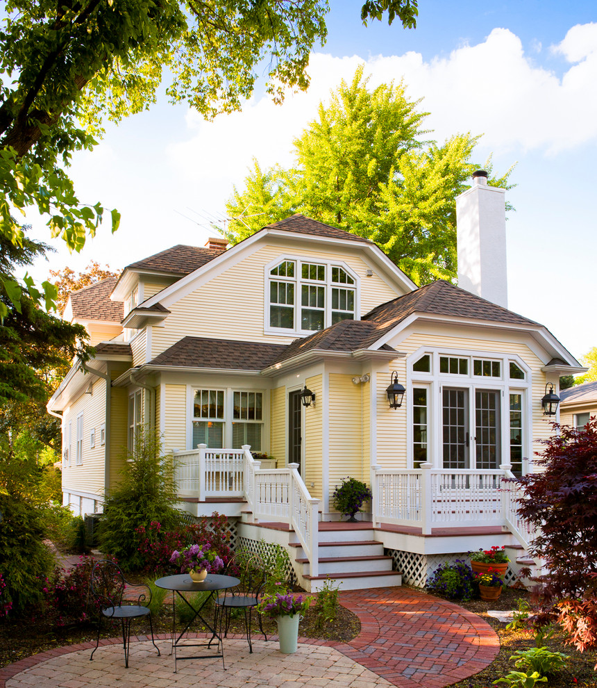 Inspiration for a timeless yellow two-story exterior home remodel in Chicago with a clipped gable roof