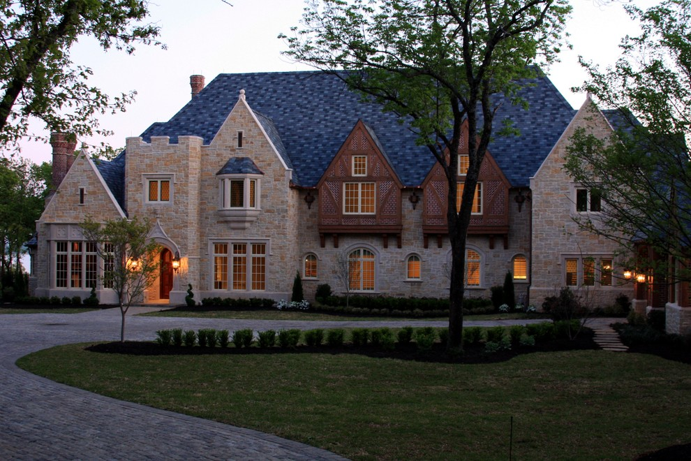 Inspiration for a large timeless beige two-story stone house exterior remodel in Dallas