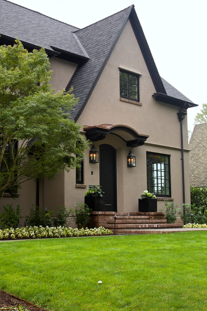 Inspiration for a large timeless beige two-story stucco gable roof remodel in Portland