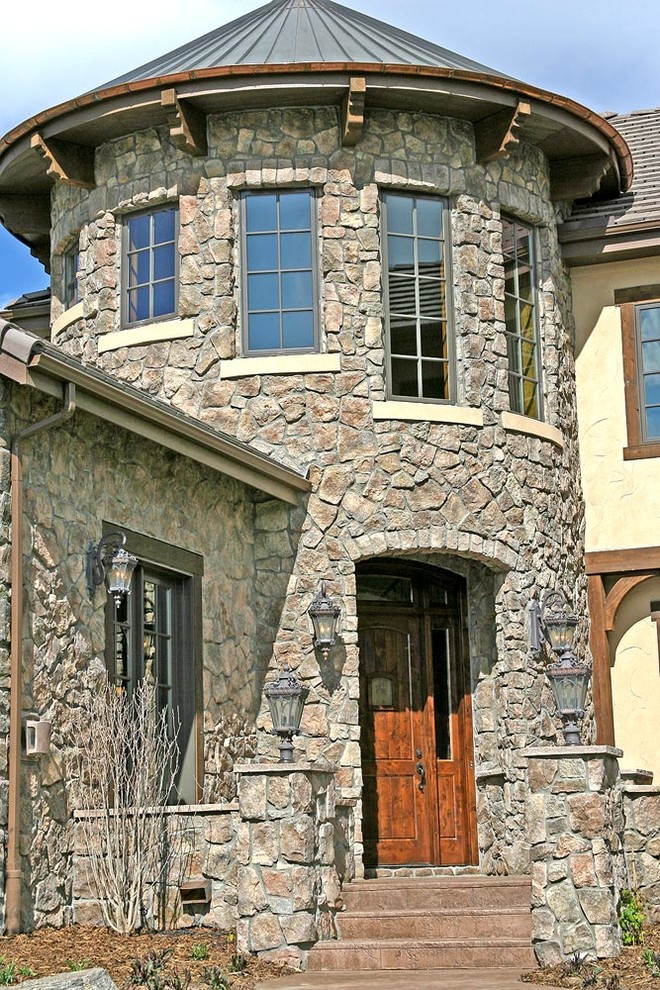 Large mediterranean two-story stone exterior home idea in Denver