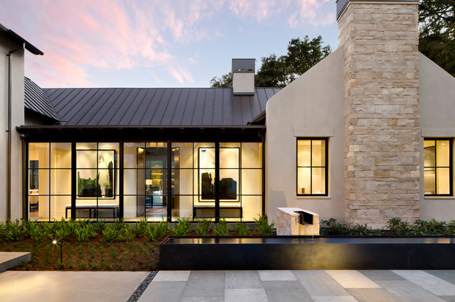 Example of a large minimalist beige one-story stucco house exterior design in San Francisco with a metal roof