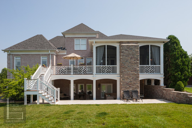 Two story double porch with outdoor fireplace, travertine patio, and AZEK deck contemporary-exterior