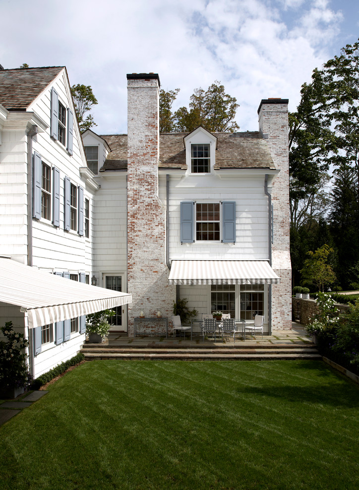 Large traditional white two-story wood gable roof idea in New York