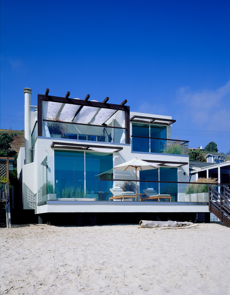 Mid-sized beach style two-story glass flat roof photo in Los Angeles