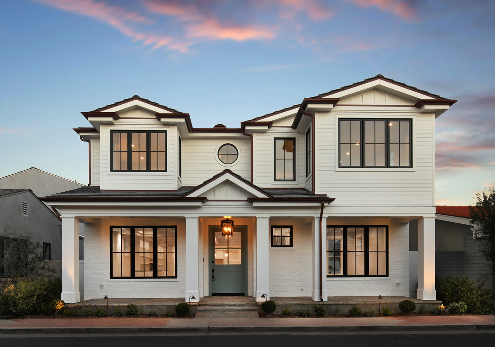 Example of a transitional white two-story exterior home design in Orange County with a shingle roof