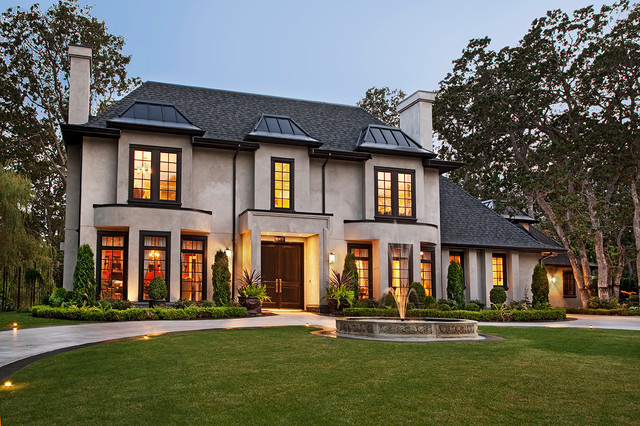 Large traditional beige two-story stucco house exterior idea in Vancouver with a shingle roof