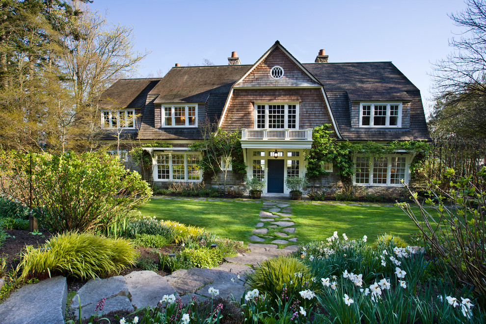 Example of an ornate two-story wood exterior home design in Seattle with a gambrel roof and a shingle roof