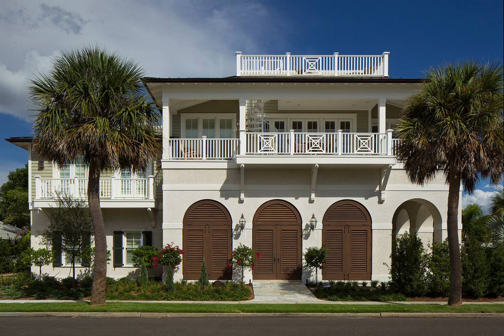 Island style beige two-story exterior home photo in Tampa with a hip roof