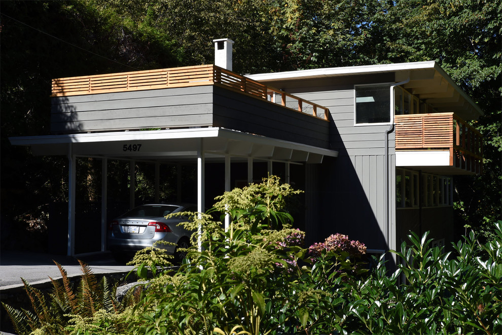 Inspiration for a mid-sized 1960s gray three-story wood flat roof remodel in Vancouver