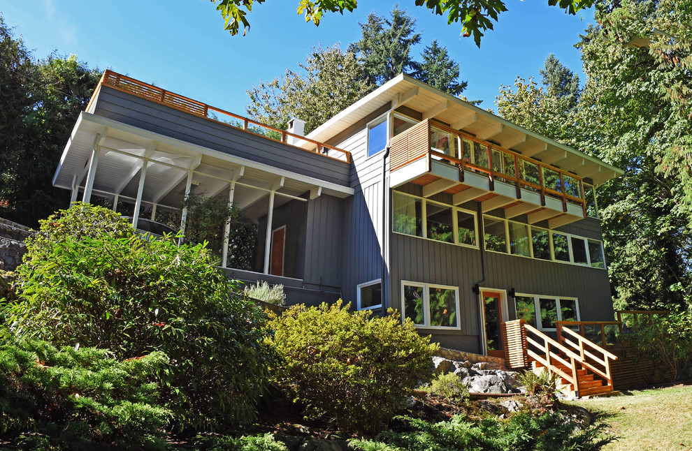 Inspiration for a mid-sized 1950s gray three-story wood flat roof remodel in Vancouver