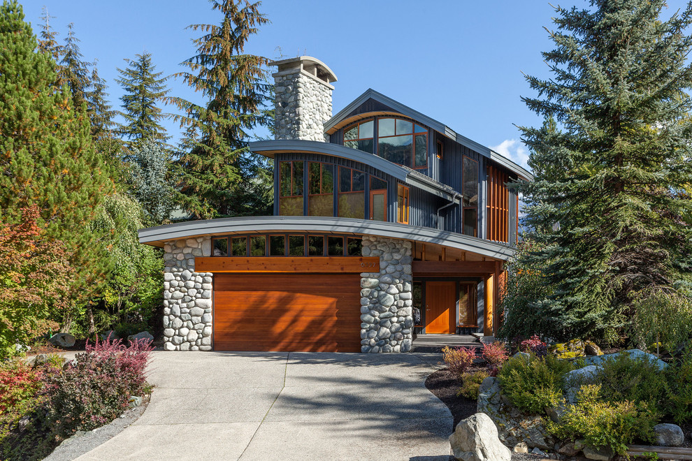 Large minimalist gray three-story mixed siding exterior home photo in Vancouver with a metal roof