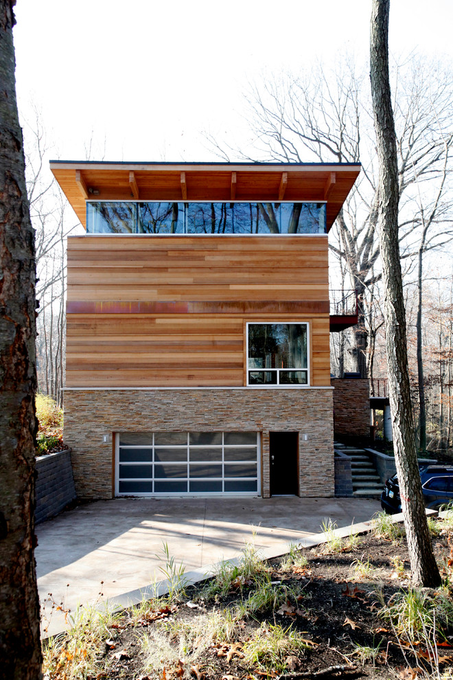 Example of a large minimalist brown three-story wood exterior home design in Other with a metal roof