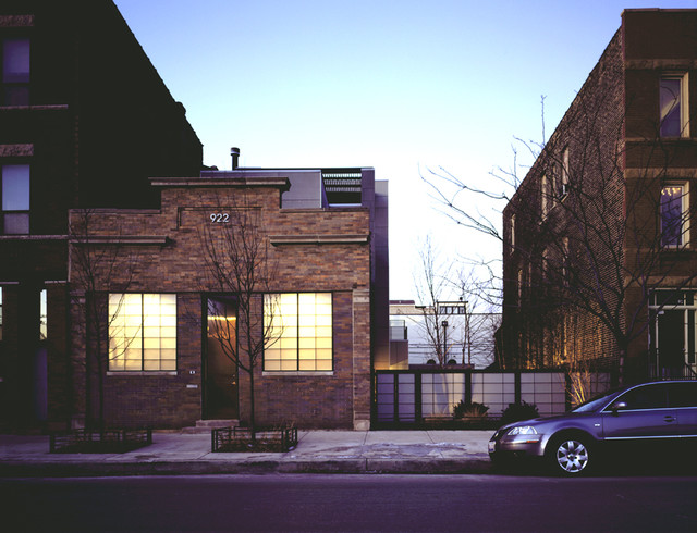 Example of a trendy beige three-story brick flat roof design in Chicago