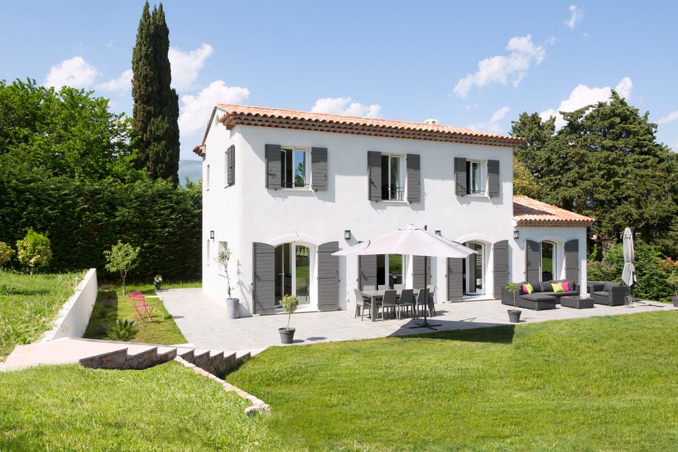 Aménagement d'une façade de maison blanche méditerranéenne à un étage et de taille moyenne avec un toit à deux pans et un toit en tuile.