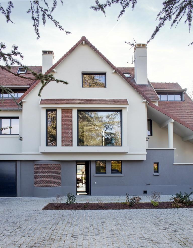 Réalisation d'une grand façade en brique beige design à deux étages et plus avec un toit à deux pans.