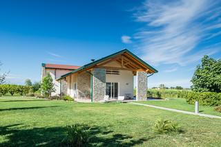 Una villa in legno immersa nel verde della campagna con portico