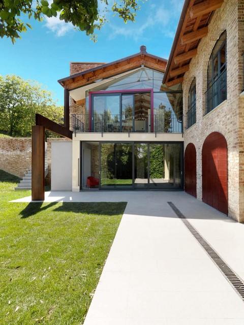 Ispirazione per la facciata di una casa grande marrone country a due piani con rivestimento in mattoni e tetto a capanna