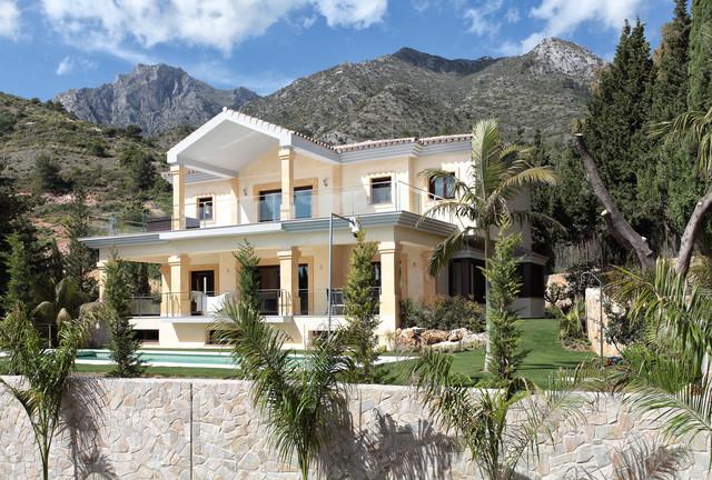 Diseño de fachada beige, mediterránea, grande, de dos plantas, con revestimiento de estuco y tejado a dos aguas