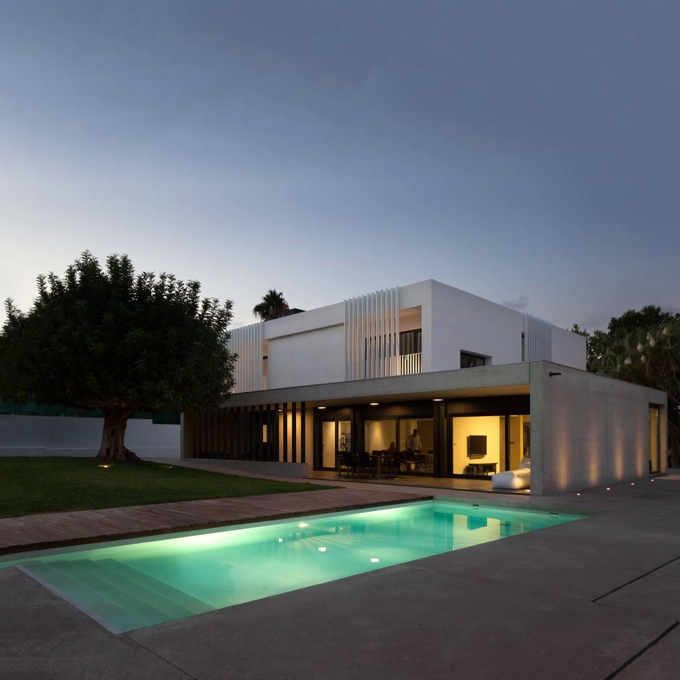 Ejemplo de fachada de casa blanca, moderna, de dos plantas, con revestimiento de hormigón y tejado plano