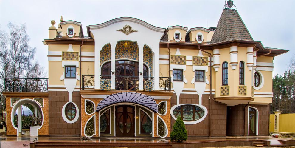 Ejemplo de fachada amarilla, tradicional, de tamaño medio, de tres plantas, con revestimientos combinados y tejado a cuatro aguas