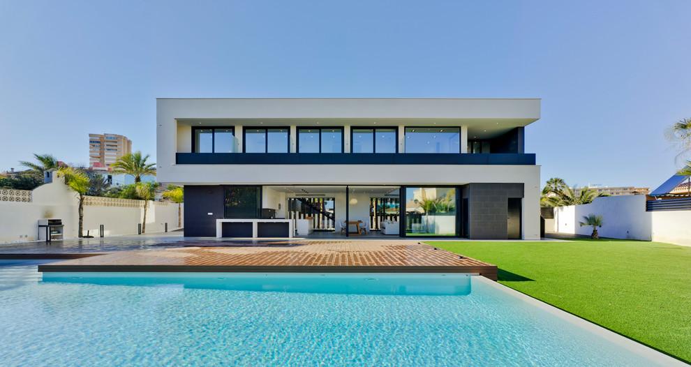 Imagen de fachada de casa blanca, contemporánea, de dos plantas, con revestimientos combinados y tejado plano