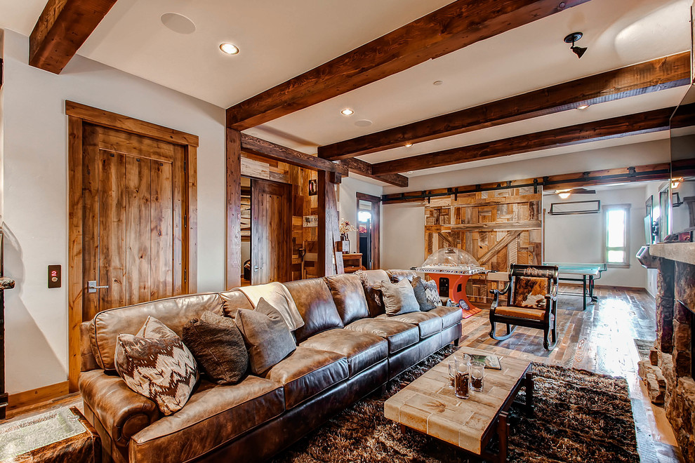 Example of a mountain style open concept dark wood floor game room design in Denver with beige walls