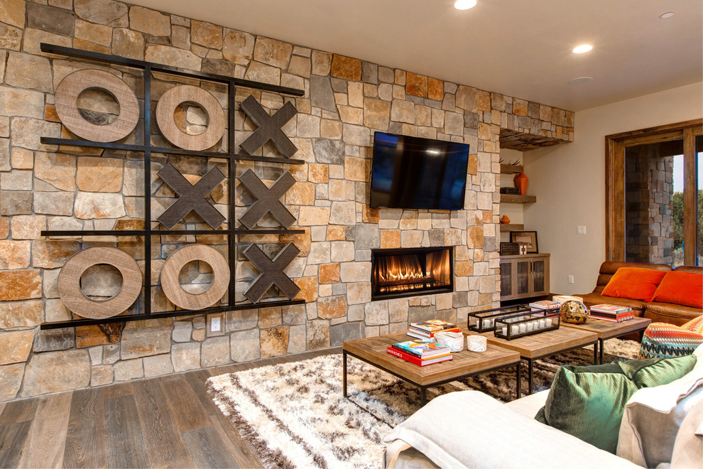 Family room - rustic medium tone wood floor family room idea in Salt Lake City with a ribbon fireplace, a stone fireplace and a wall-mounted tv