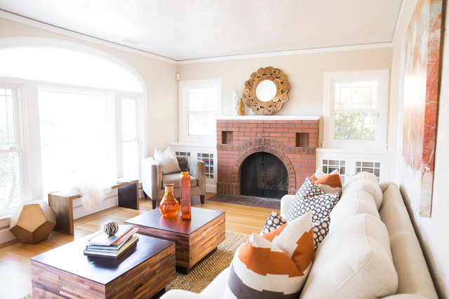 Example of a transitional medium tone wood floor family room design in Sacramento with beige walls, a standard fireplace and a brick fireplace