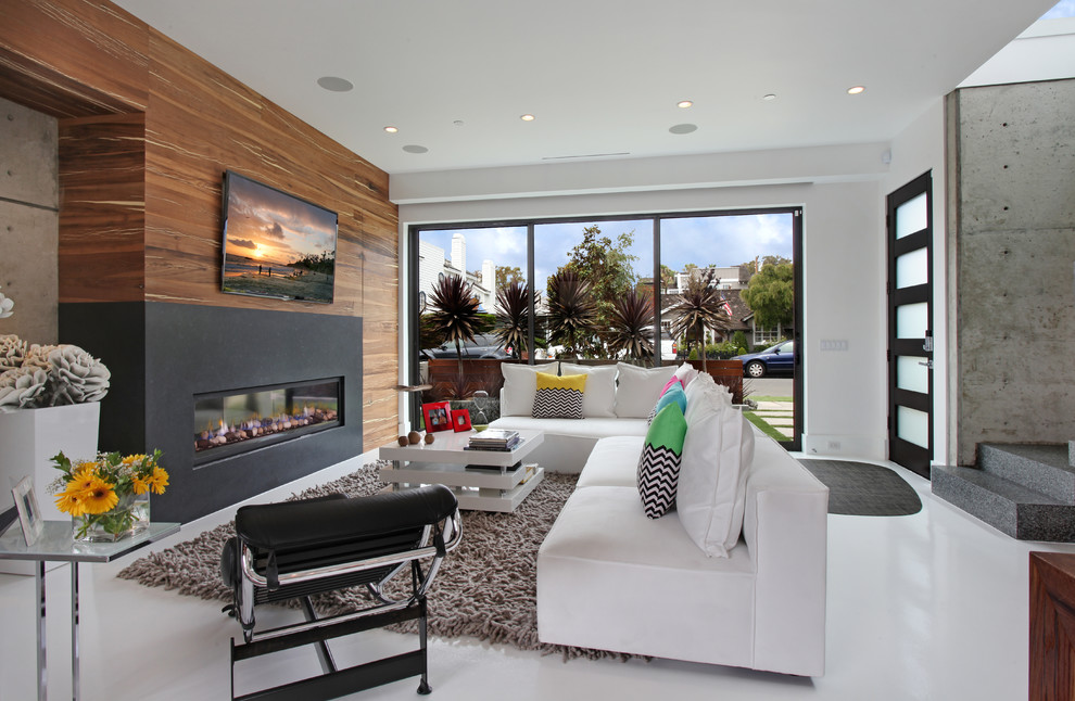 Trendy white floor family room photo in Orange County with white walls, a ribbon fireplace and a wall-mounted tv