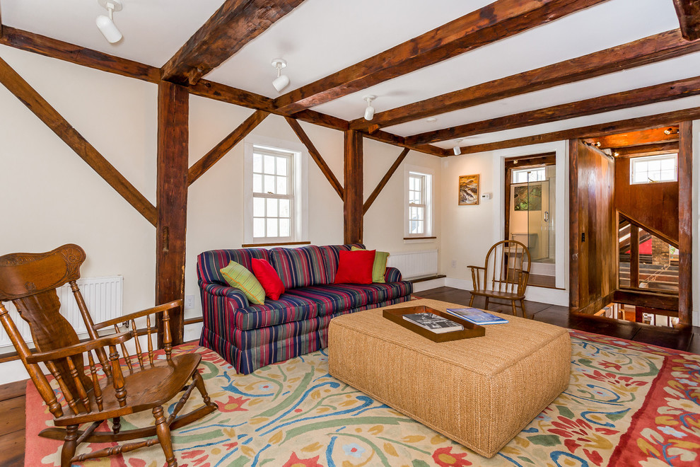 Example of a country enclosed dark wood floor and brown floor family room design in Boston with white walls