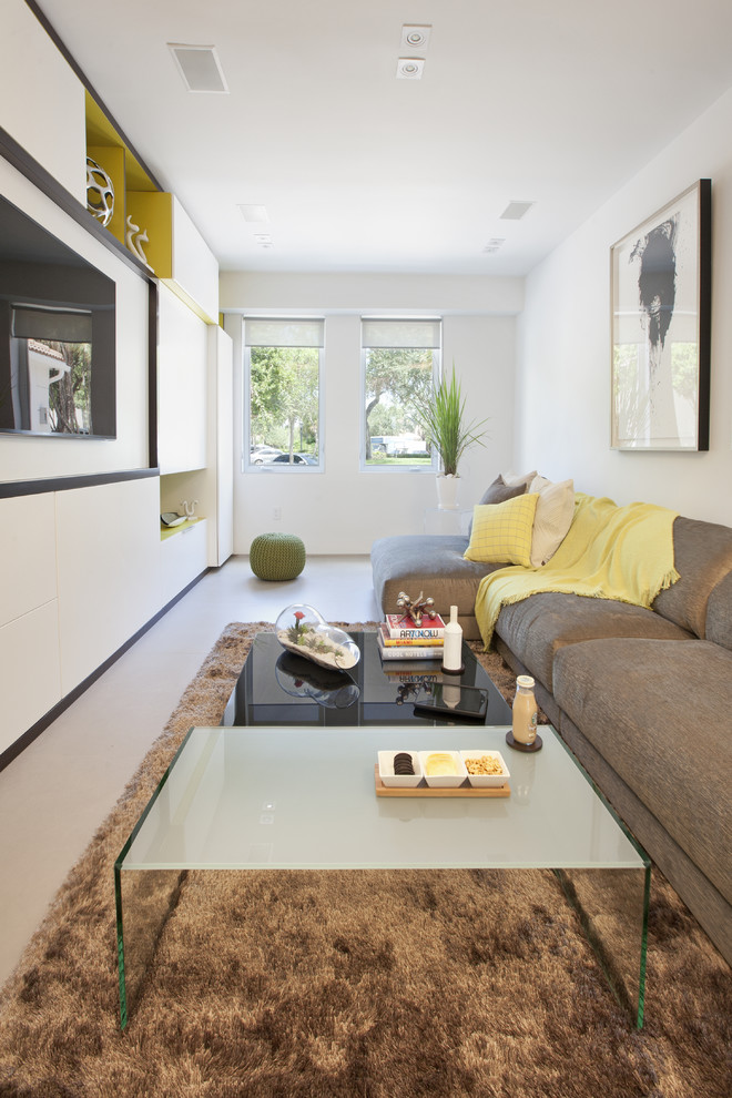 Trendy enclosed family room photo in Miami with white walls and a wall-mounted tv