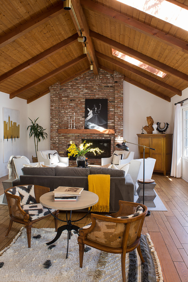 Mid-sized transitional open concept light wood floor and brown floor family room photo in Los Angeles with white walls, a standard fireplace, a brick fireplace and a concealed tv