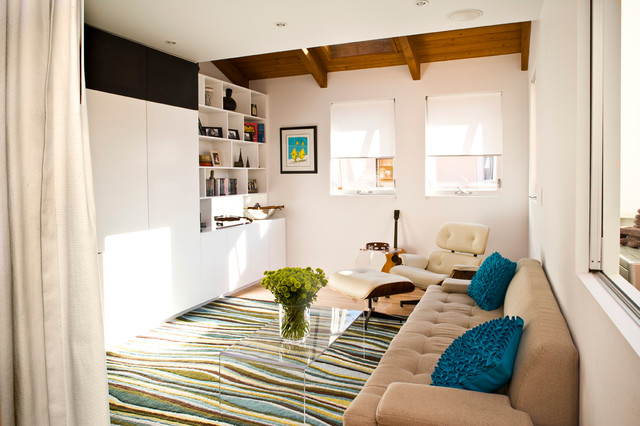 Family room - contemporary carpeted family room idea in Los Angeles with white walls