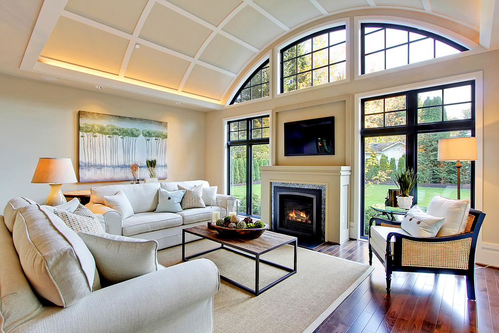 Trendy medium tone wood floor family room photo in Seattle with beige walls, a standard fireplace, a tile fireplace and a wall-mounted tv