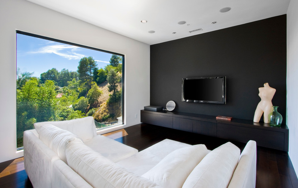 Inspiration for a contemporary open concept dark wood floor and brown floor family room remodel in Los Angeles with black walls and a wall-mounted tv