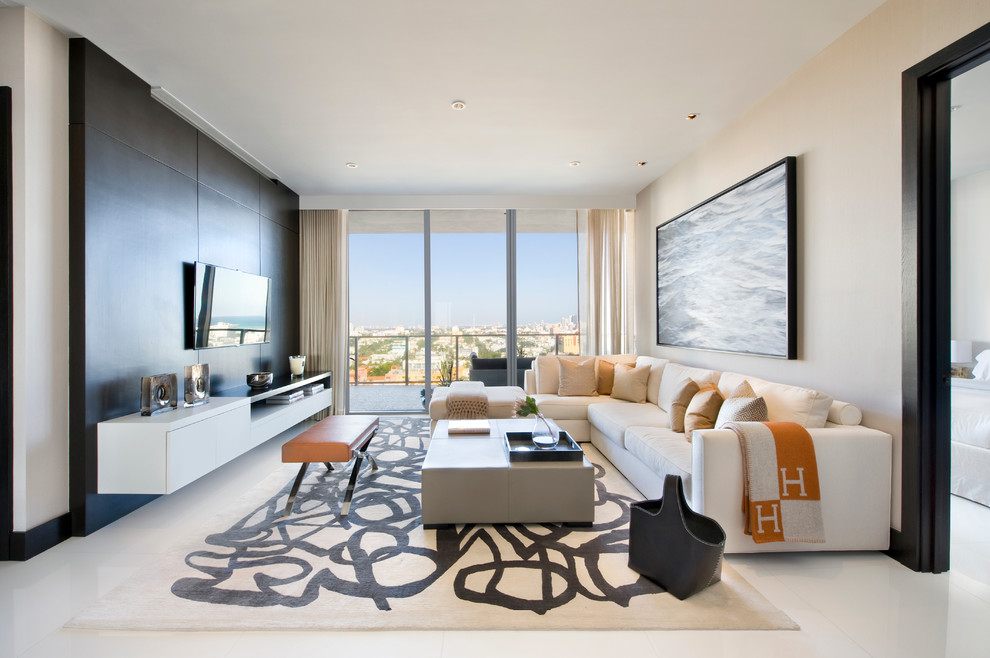 Inspiration for a contemporary open concept family room remodel in Miami with beige walls and a wall-mounted tv