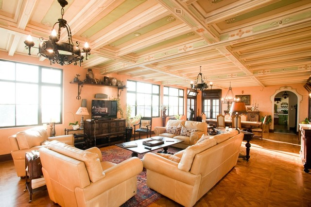 Inspiration for a timeless open concept medium tone wood floor family room remodel in San Diego with orange walls and a tv stand