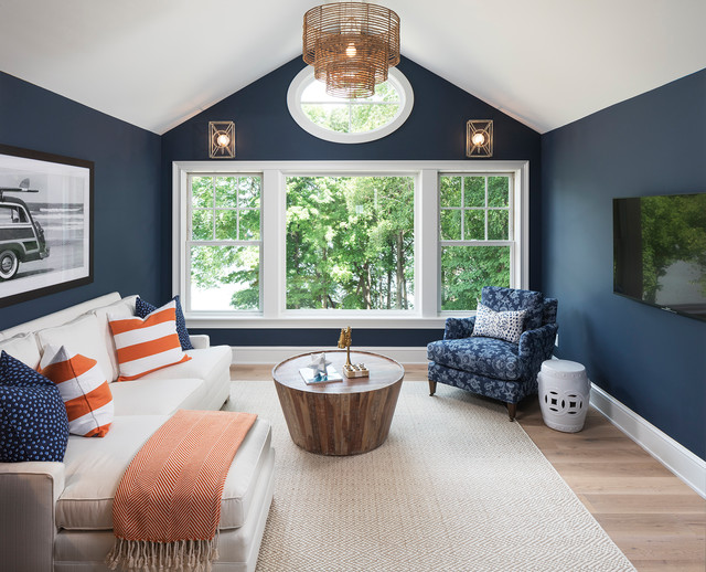 This is an example of a nautical family and games room in Minneapolis with blue walls, light hardwood flooring, no fireplace and a wall mounted tv.