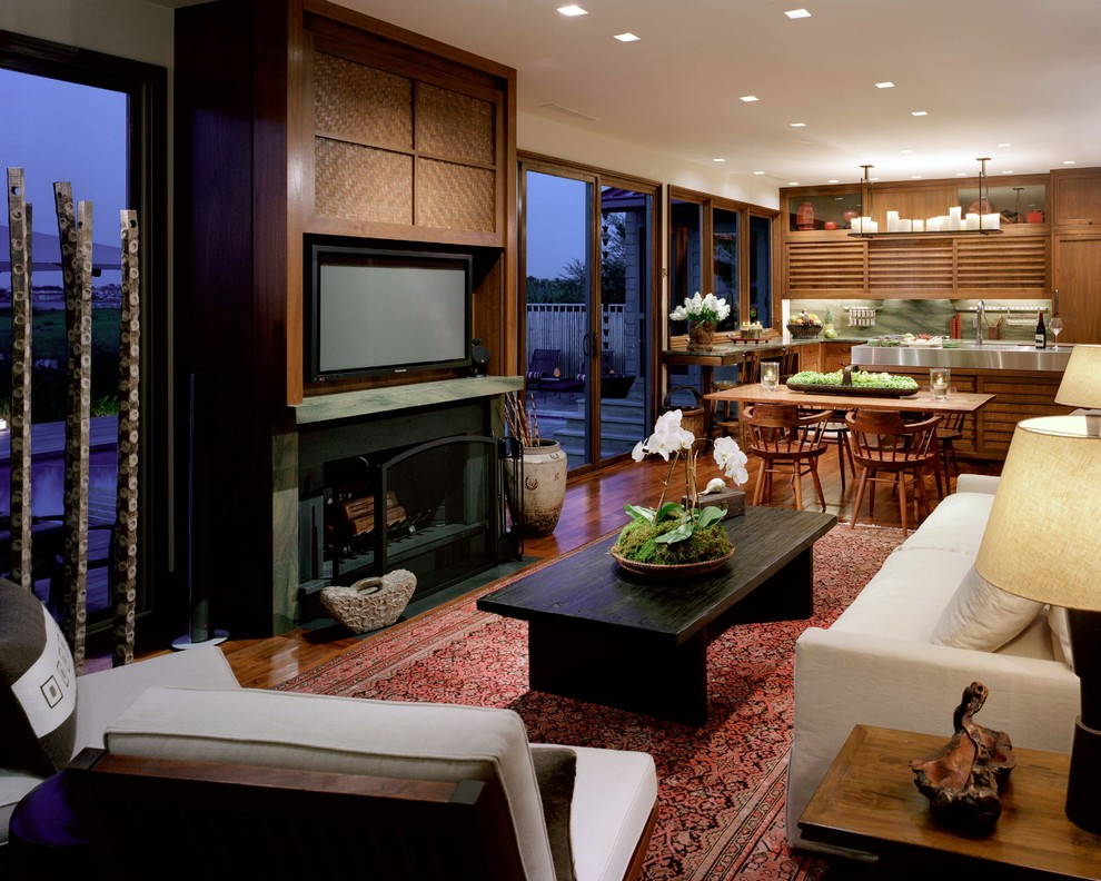 Open concept medium tone wood floor family room photo in New York with a standard fireplace and a concealed tv