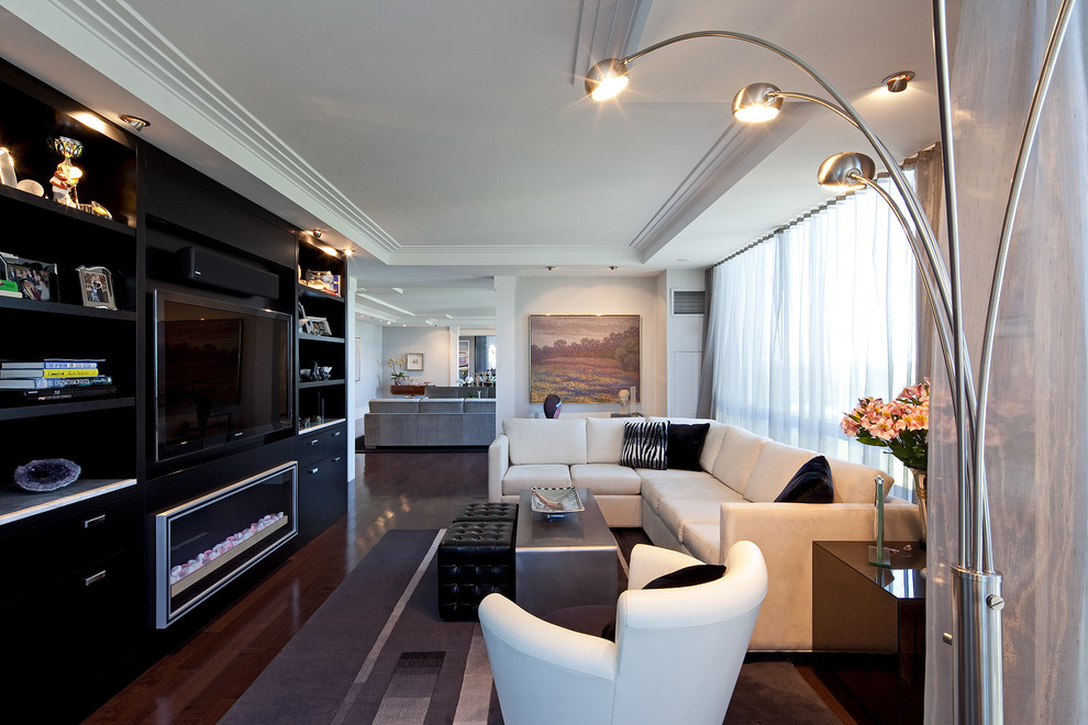 Trendy open concept dark wood floor family room photo in Toronto with white walls and a media wall
