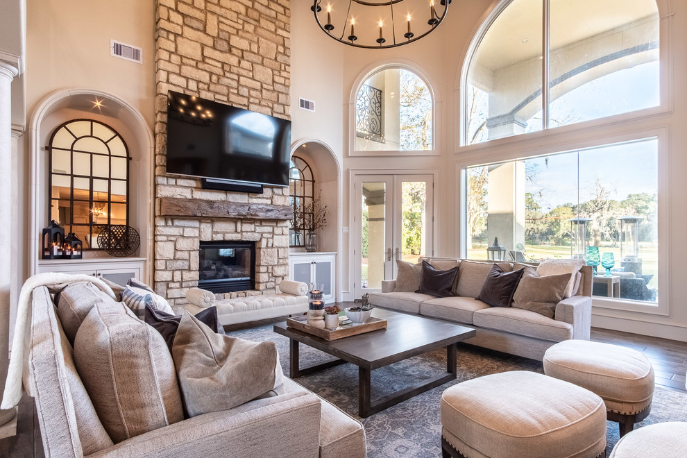 Large open concept porcelain tile and brown floor family room photo in Houston with a two-sided fireplace, a stone fireplace and a wall-mounted tv