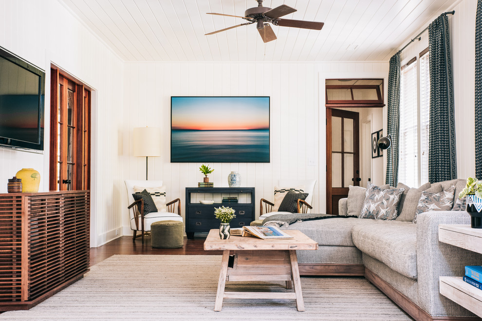 Example of a beach style dark wood floor and brown floor family room design in Charleston with white walls and a wall-mounted tv