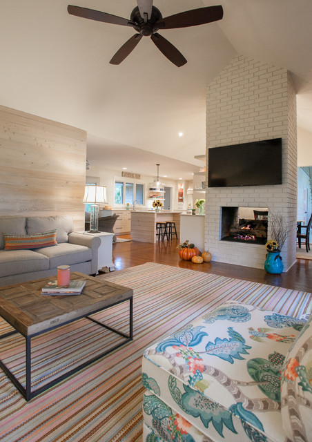 Inspiration for a beach style open concept medium tone wood floor family room remodel in Charleston with a two-sided fireplace, a brick fireplace and a wall-mounted tv