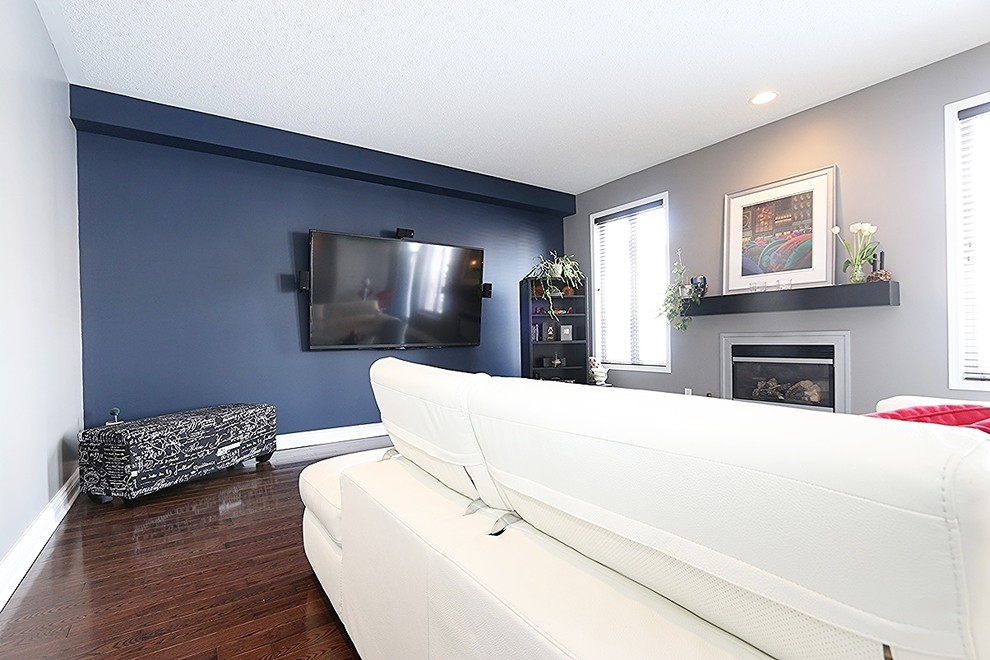 Example of a mid-sized minimalist enclosed dark wood floor family room design in Ottawa with blue walls, a wall-mounted tv and a standard fireplace