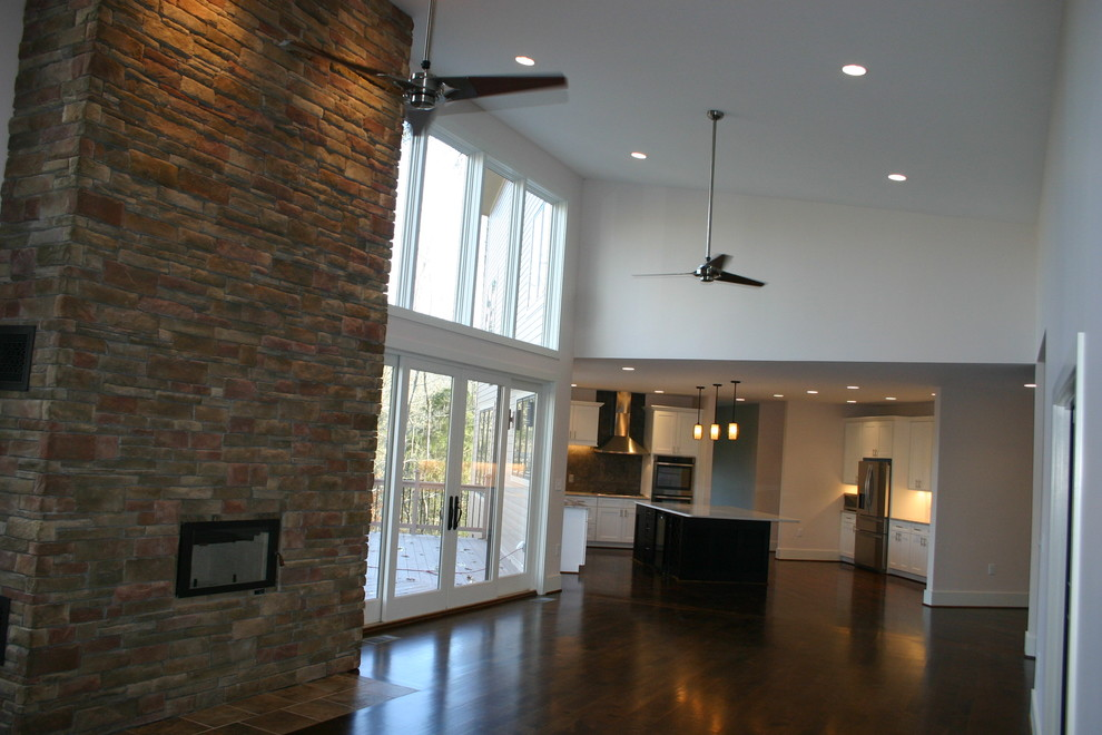 Large trendy open concept dark wood floor family room photo in Raleigh with a wall-mounted tv, beige walls, a standard fireplace and a stone fireplace