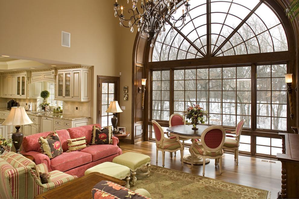 Elegant open concept medium tone wood floor family room photo in Minneapolis with beige walls and no tv