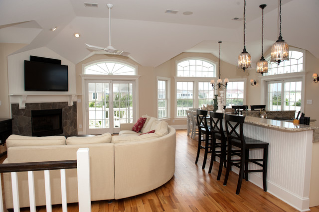 Example of a large coastal open concept light wood floor family room design in Other with beige walls and a wall-mounted tv
