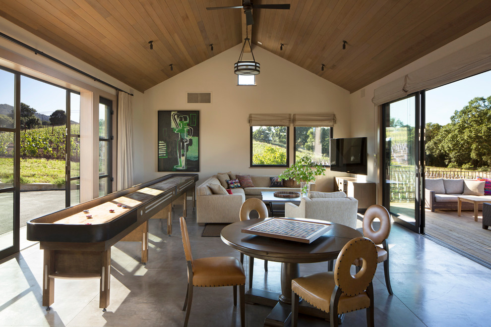 Transitional concrete floor game room photo in San Francisco with beige walls