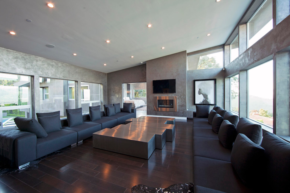 Trendy open concept dark wood floor family room photo in Los Angeles with gray walls, a metal fireplace and a wall-mounted tv